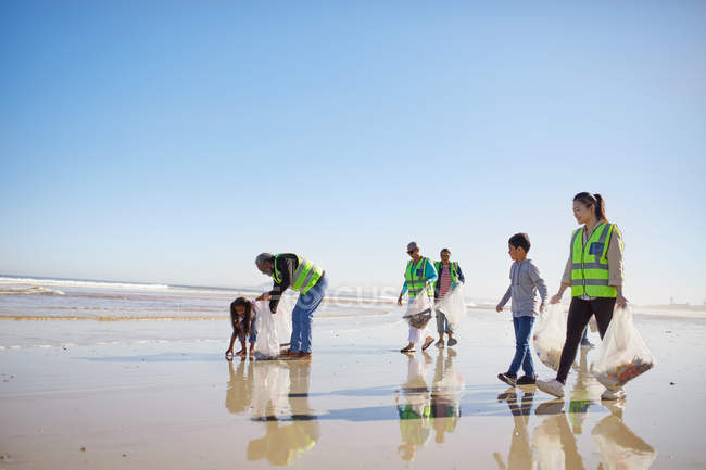 Volunteers cleaning litter from wet sand beach — Stock Photo