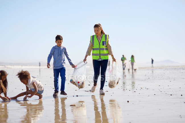 Mother and son volunteers cleaning up litter on sunny wet sand beach — Stock Photo