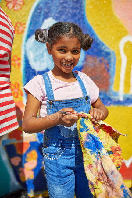 Portrait smiling girl painting vibrant mural on sunny wall — Stock Photo