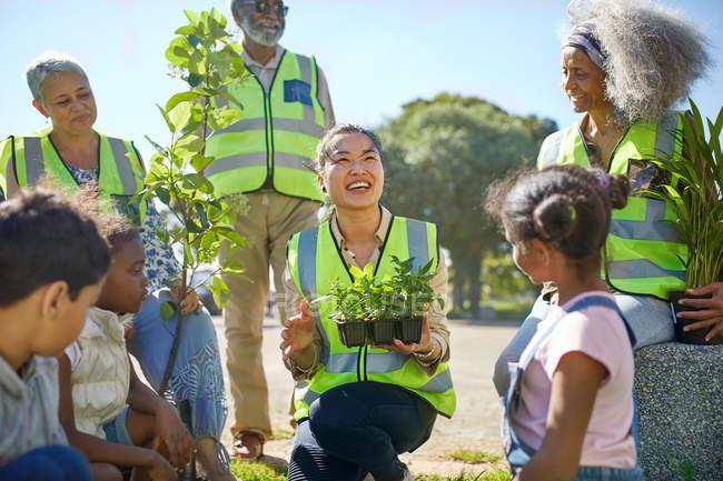 Des bénévoles heureux plantent des arbres et des plantes dans un parc ensoleillé — Photo de stock