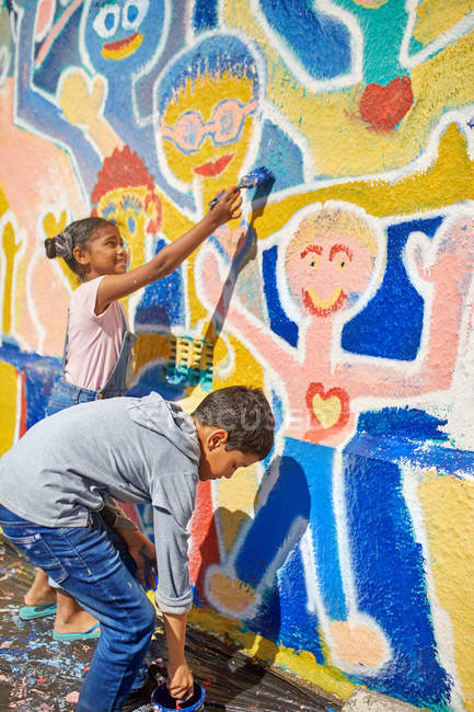 Children painting vibrant mural on sunny wall — Stock Photo