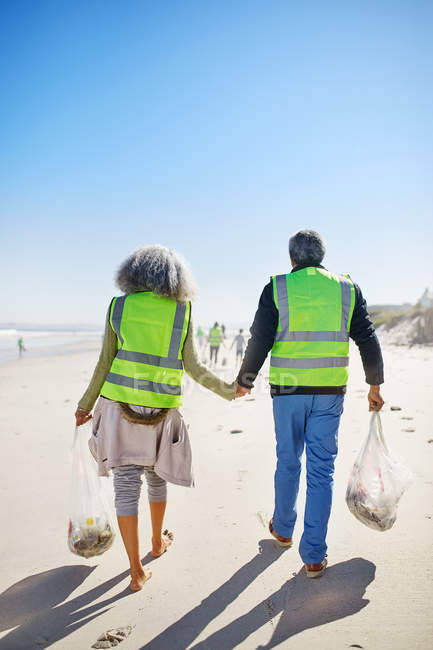 Affettuosi volontari anziani coppia ripulire lettiera sulla spiaggia di sabbia soleggiata e bagnata — Foto stock