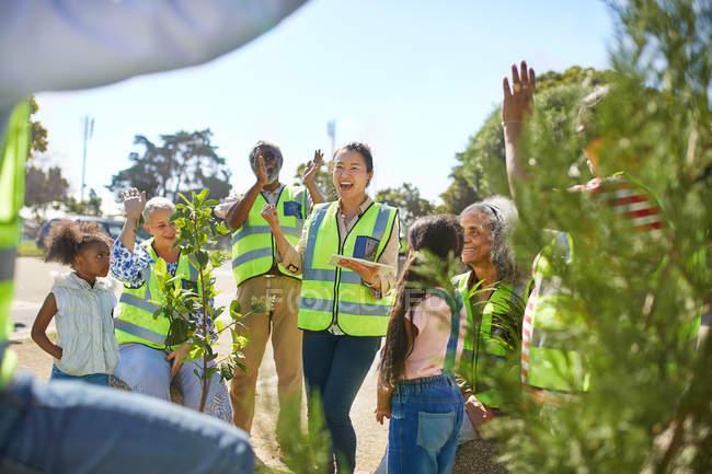 Des bénévoles enthousiastes applaudissent, plantent des arbres dans un parc ensoleillé — Photo de stock