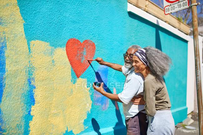 Счастливая старшая пара рисует фреску в форме сердца на солнечной стене — стоковое фото