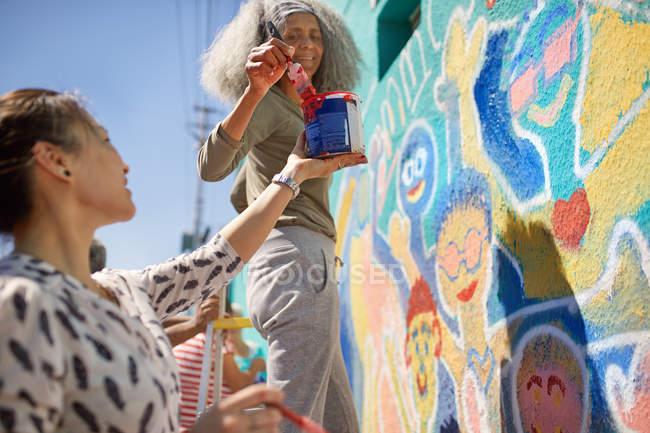 Female volunteers painting vibrant community mural on sunny urban wall — Stock Photo