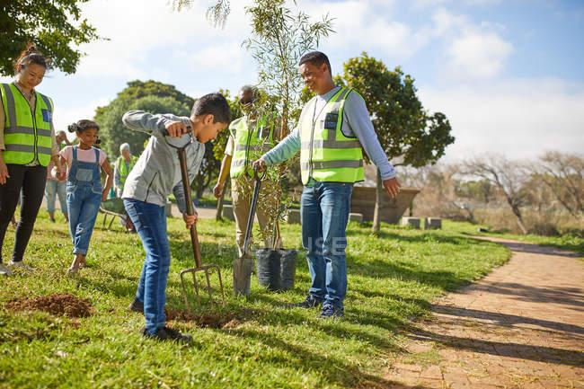 Voluntários familiares de várias gerações plantando árvores no parque ensolarado — Fotografia de Stock