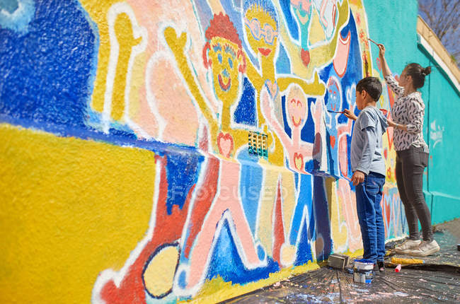 Mother and son volunteers painting vibrant mural on sunny wall — Stock Photo