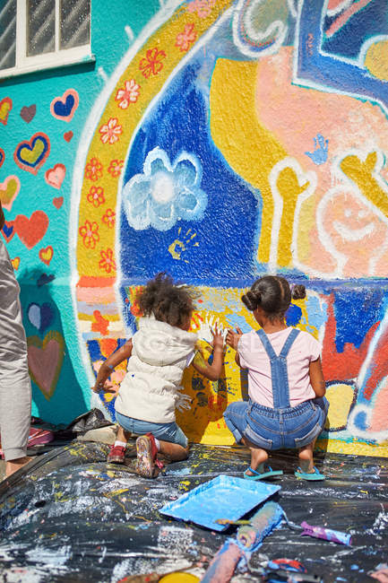 Girls painting vibrant mural on sunny wall — Stock Photo