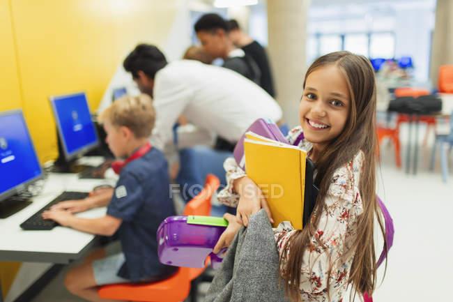 Retrato de un estudiante joven sonriente y confiado llevando libros en la biblioteca - foto de stock