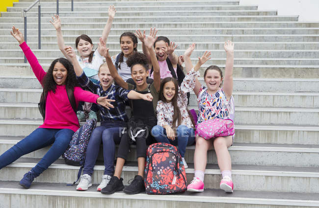 Portrait enthusiastic junior high girl students waving on steps — Stock Photo