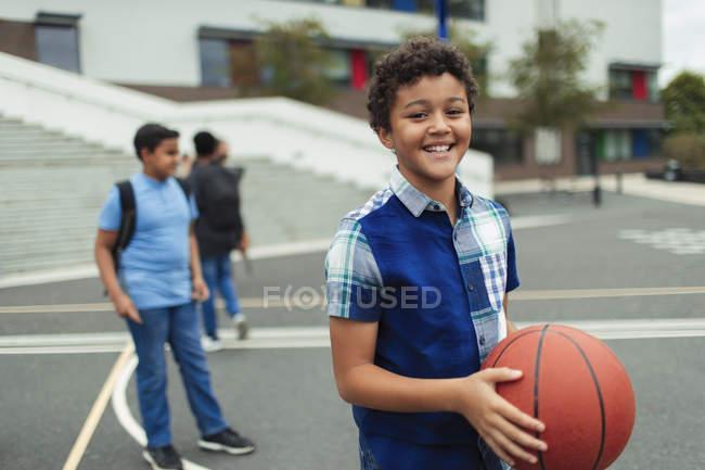 Портрет улыбающийся, уверенный в себе мальчик, играющий в баскетбол на школьном дворе — стоковое фото