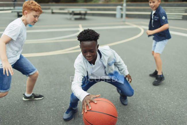 Мальчики играют в баскетбол на школьном дворе — стоковое фото