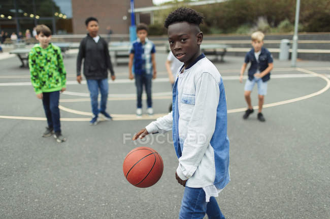 Портрет уверенного африканского мальчика, играющего в баскетбол на школьном дворе — стоковое фото