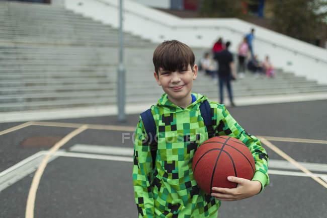 Портрет уверенный подросток с баскетболом на школьном дворе — стоковое фото