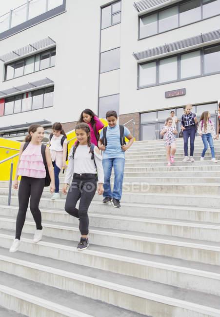 Studenti delle medie che lasciano l'edificio scolastico, gradini discendenti — Foto stock