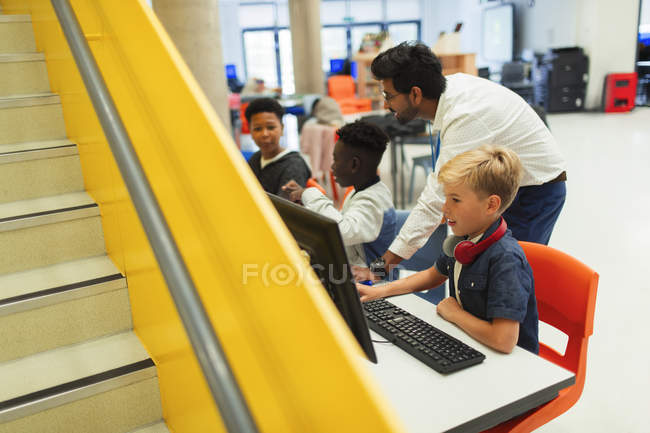 Teacher helping junior high students using computers in library — Stock Photo