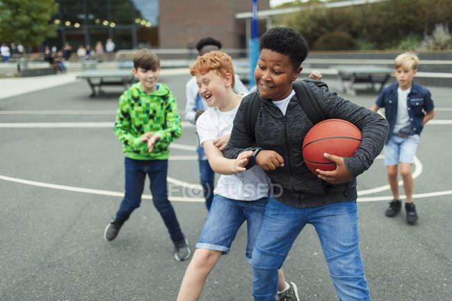 Счастливые мальчики играют в баскетбол на школьном дворе — стоковое фото