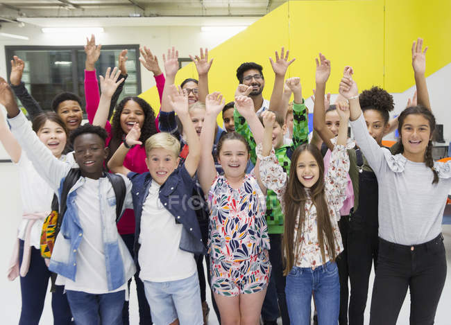 Portrait enthusiastic junior high students and teachers cheering with arms raised — Stock Photo