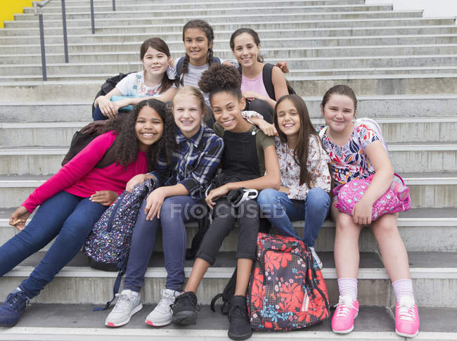Portrait confident junior high female students on steps — Stock Photo