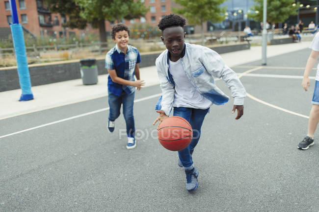 Tween boys playing basketball in schoolyard — Stock Photo