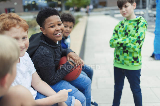 Happy boys with basketball ball in schoolyard — Stock Photo
