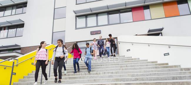 Studenti delle scuole medie che lasciano l'edificio scolastico, gradini decrescenti — Foto stock