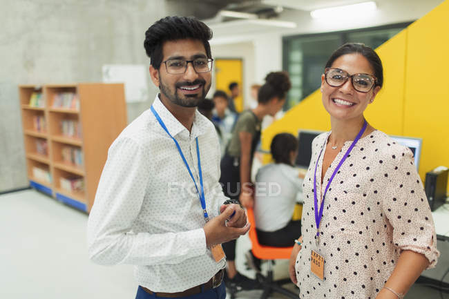 Portrait smiling, confident junior high teachers in library — Stock Photo