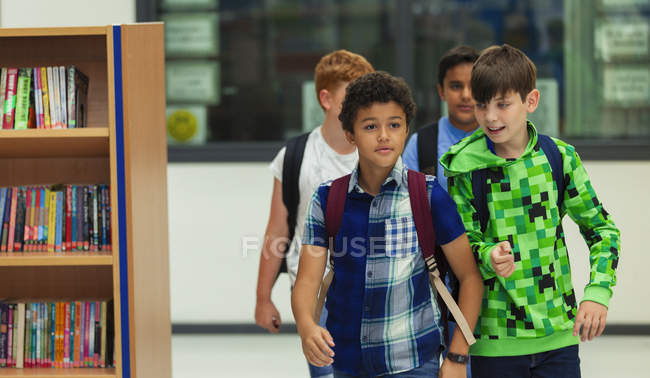 Junior high boy students walking in library — Stock Photo