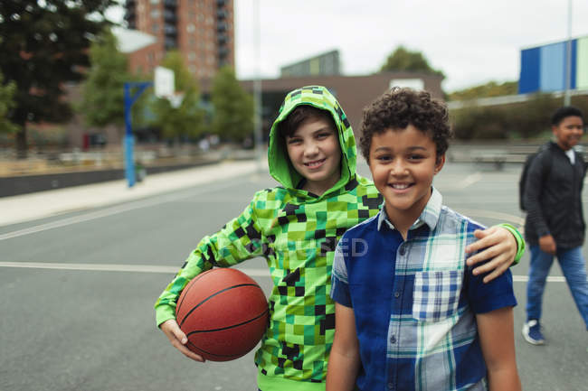 Portrait of happy junior high friends playing basketball in schoolyard — Stock Photo