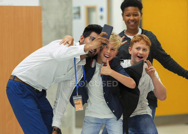 Junior high boy students and male teacher taking selfie with smart phone — Stock Photo