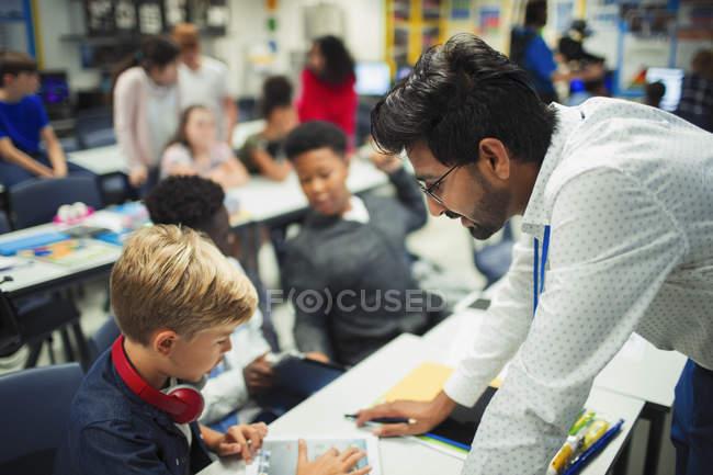 Profesor masculino ayudando a estudiante de secundaria usando tableta digital en el aula - foto de stock