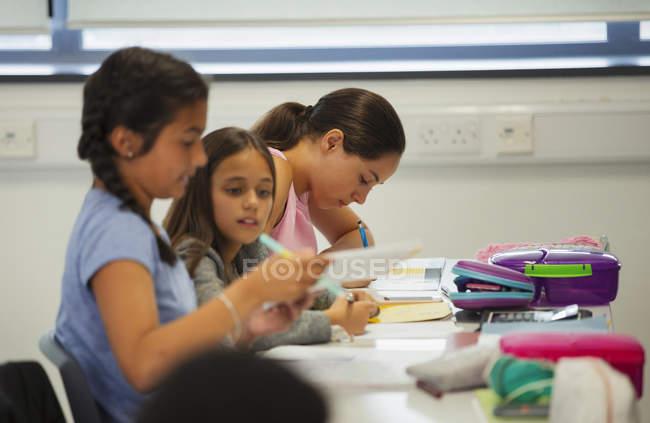 Studenti delle scuole medie che studiano alla scrivania in classe — Foto stock
