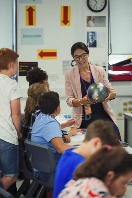 Insegnante di geografia femminile con lezioni di insegnamento in globo in classe — Foto stock