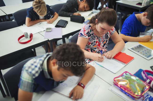 Studenti delle scuole superiori che fanno compiti a casa alle scrivanie in classe — Foto stock