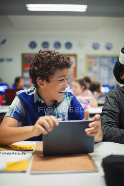 Heureux garçon de l'école primaire en utilisant une tablette numérique en classe — Photo de stock