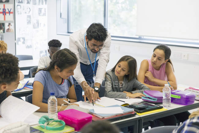 Male teacher helping junior high school students at desk in classroom — Foto stock