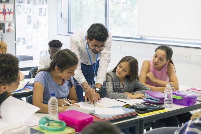 Insegnante maschile aiutare gli studenti delle scuole medie alla scrivania in classe — Foto stock