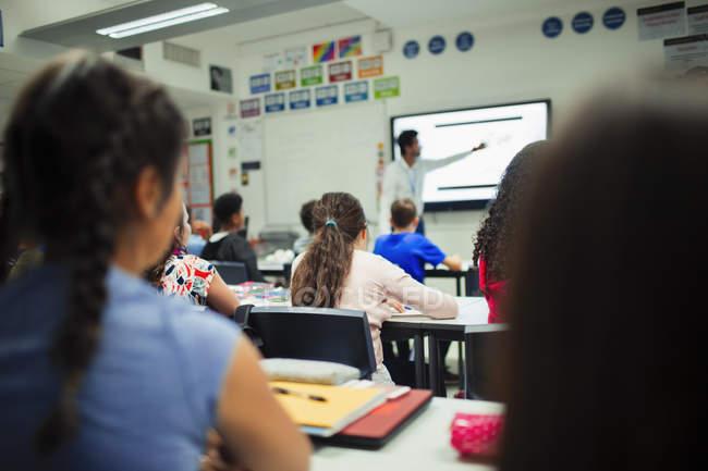 Studenti delle scuole medie che guardano l'insegnante dare lezione allo schermo di proiezione in classe — Foto stock