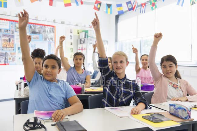 Studenti delle scuole medie ansiosi con le mani alzate in classe — Foto stock