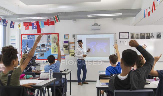 Studenti delle scuole medie alzando la mano per la lezione di guida degli insegnanti in classe — Foto stock