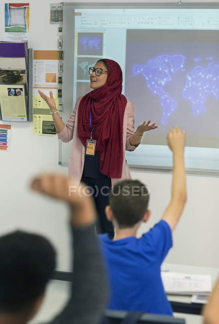 Female teacher in hijab leading lesson at projection screen in classroom — Stock Photo