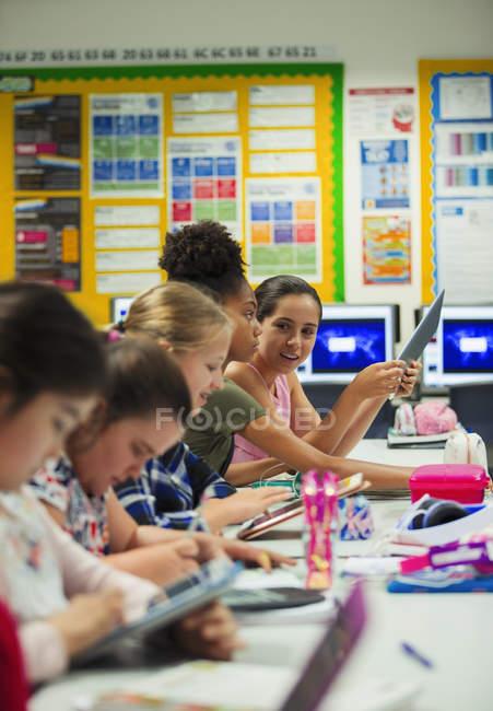 Молодший середньої школи дівчина студент використанням цифрової таблетки на столі в класі — стокове фото
