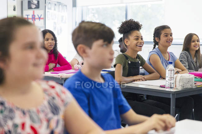Sorridenti studenti delle scuole medie che ascoltano in classe — Foto stock