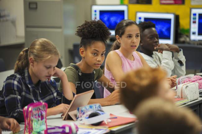 Focused scuola media studente ragazza ascolto in classe — Foto stock