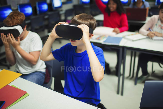 Étudiants de lycée de junior utilisant des simulateurs de réalité virtuelle dans la salle de classe — Photo de stock
