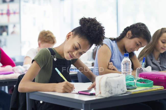 Sicura studentessa delle scuole medie che fa i compiti in classe — Foto stock
