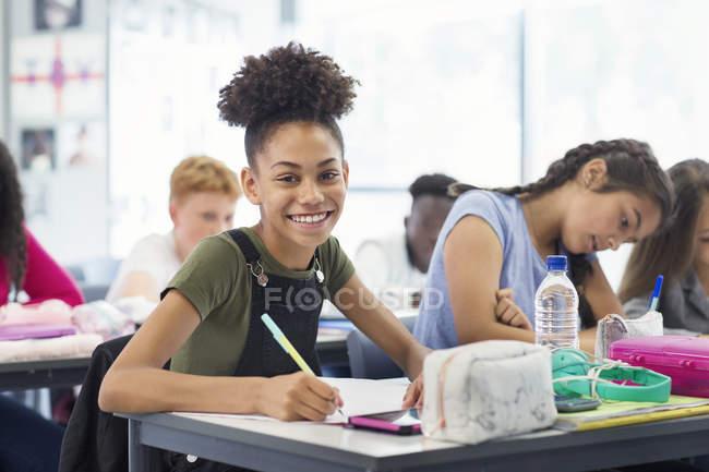 Portrait of confident junior high school student doing homework in classroom — Foto stock
