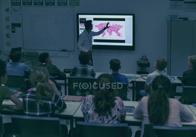 Schüler beobachten Geographielehrer an der Projektionsfläche im dunklen Klassenzimmer — Stockfoto