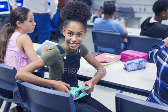 Portrait smiling, confident junior high school girl student with headphones at desk in classroom — Stock Photo