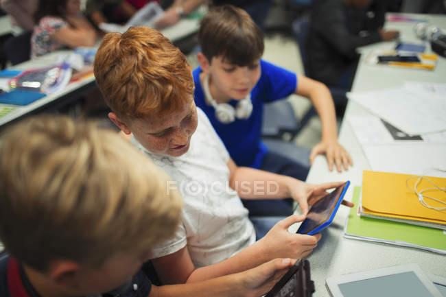 Молодший середньої школи хлопчика студентів, що використовують цифрові планшети на столі в класі — стокове фото